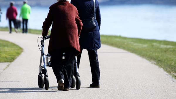 Two older people walking near water